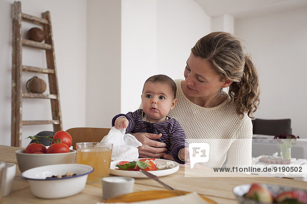 Mother looking at baby girl while sitting at table in house