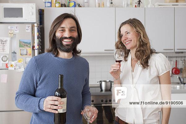 Glückliches Paar genießt Rotwein in der Küche