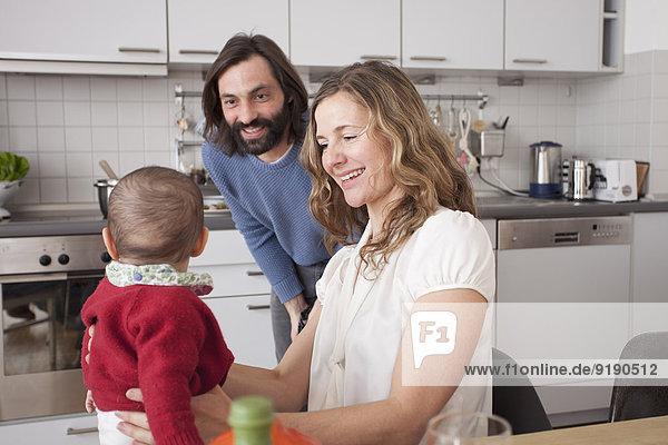 Glückliche Eltern  die das kleine Mädchen in der Küche anschauen.
