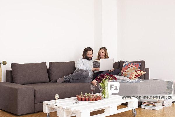 Mittleres erwachsenes Paar mit Laptop im Wohnzimmer