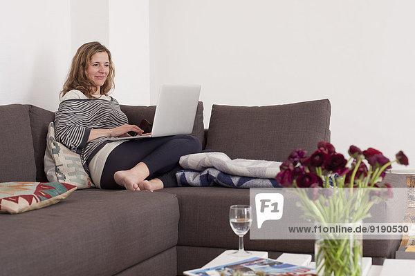 Frau mit Laptop auf Sofa im Wohnzimmer