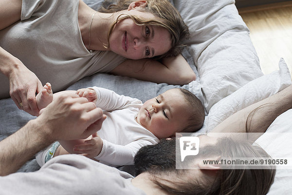Zärtliche Eltern  die das Mädchen beim Entspannen auf der Matratze anschauen.