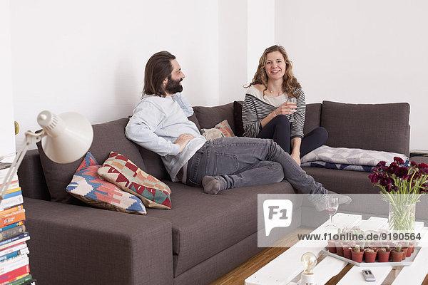 Mittleres erwachsenes Paar  das seine Freizeit im Wohnzimmer verbringt.