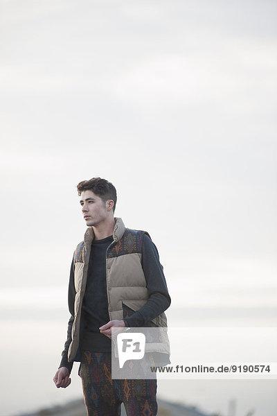 Nachdenklicher junger Mann steht gegen den Himmel.