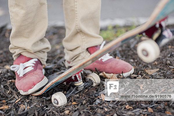 Niedrige Sektion des Mannes mit Skateboard im Freien