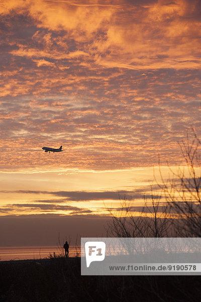 Flugzeug gegen bewölkten Himmel bei Sonnenuntergang