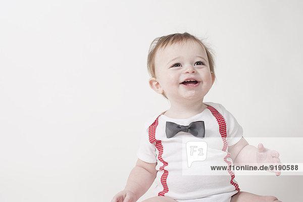 Fröhlicher kleiner Junge  der vor weißem Hintergrund wegschaut.