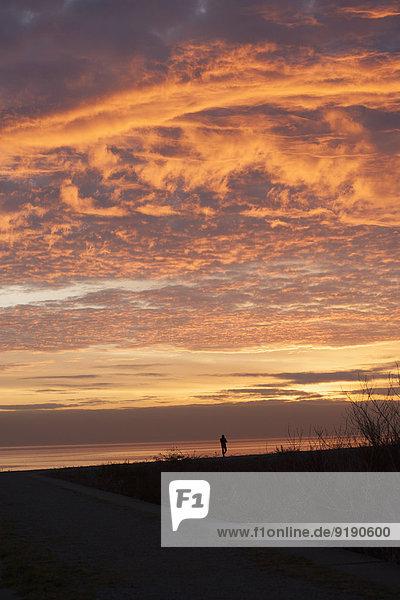 Silhouettenlandschaft vor bewölktem Himmel bei Sonnenuntergang
