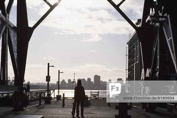 Durchgehende Rückansicht des Mannes mit Skateboard im Stadtbild
