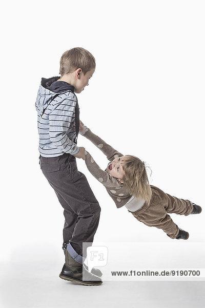 Volle Länge des Bruders spinnende Schwester vor weißem Hintergrund