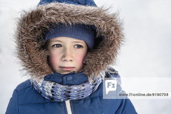 Nachdenklicher Junge in warmer Kleidung  der nach draußen schaut.
