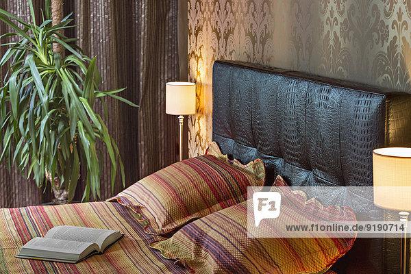 Buch und Kissen auf dem Bett