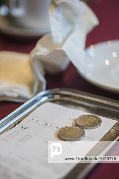 Rechnung und Trinkgeld im Teller auf dem Restauranttisch