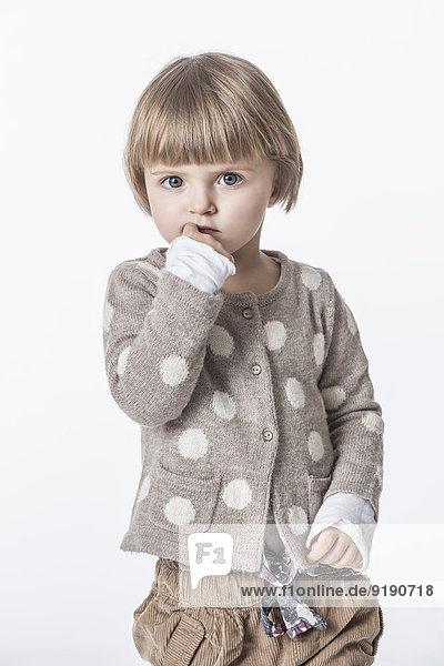 Porträt des süßen Mädchens mit Finger im Mund vor weißem Hintergrund
