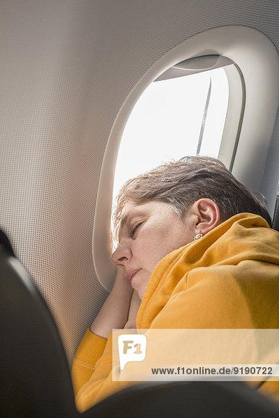 Reife Frau schläft im Flugzeug