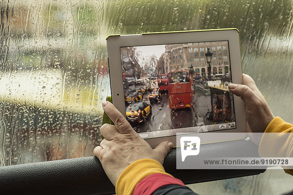 Abgeschnittenes Bild einer Frau  die einen Bus mit digitalem Tablett fotografiert.
