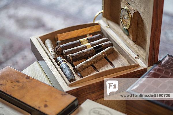 Hochwinkelansicht der Zigarren in Holzkiste auf dem Tisch