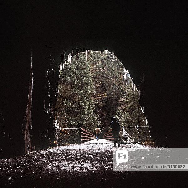 Blick auf Frauen  die durch die Höhle zur Brücke gehen Blick auf Frauen, die durch die Höhle zur Brücke gehen