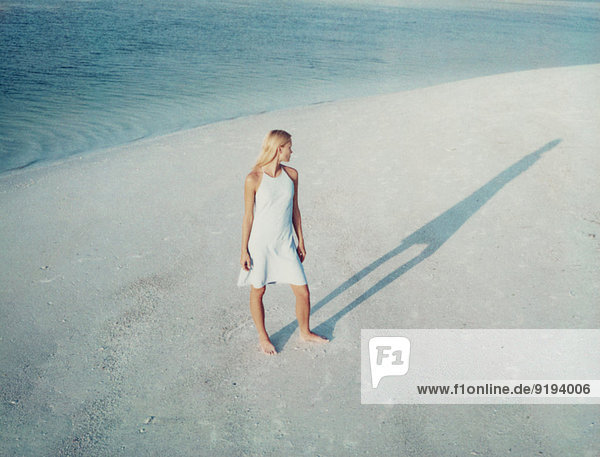Frau  die am Strand steht und ihren Schatten betrachtet.
