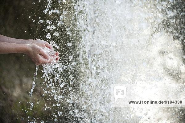 Kind hält Hände unter Wasserfall  abgeschnitten Kind hält Hände unter Wasserfall, abgeschnitten