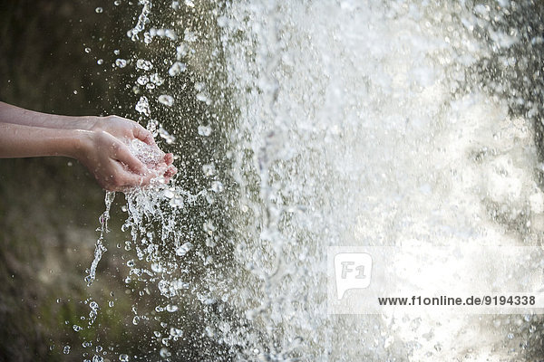 Kind hält Hände unter Wasserfall  abgeschnitten
