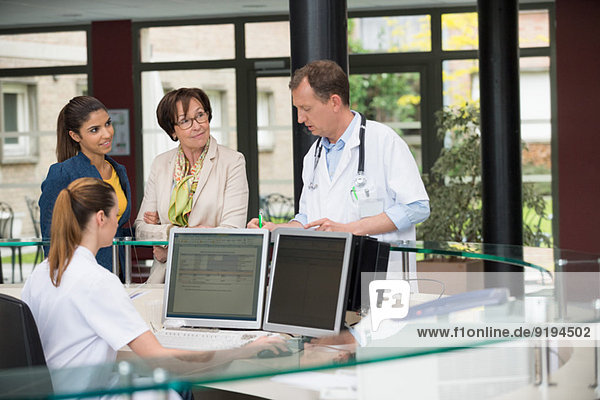 Male doctor discussing with patients at hospital reception desk
