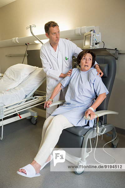 Male doctor helping female patient to sitting on chair in hospital