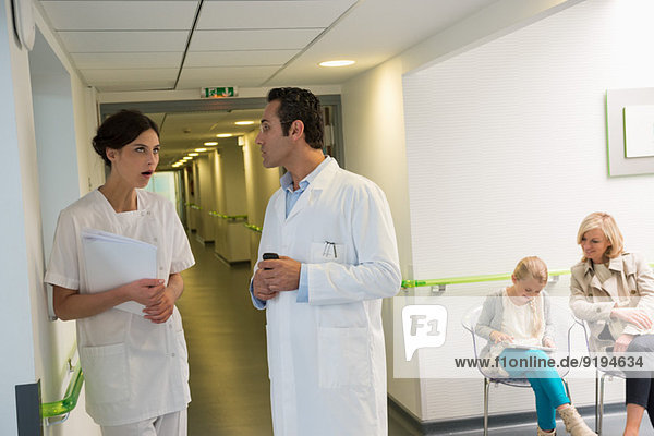 Doctor and nurse discussing in hospital corridor with patients sitting in waiting room