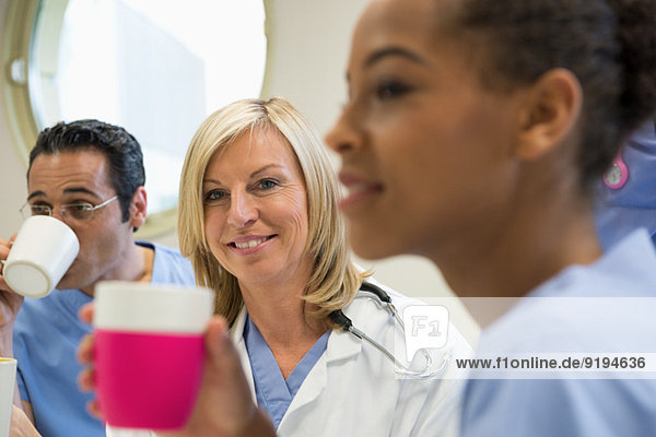 Ärzte und Krankenschwester bei einer Kaffeepause in der Krankenhauskantine