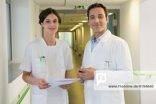 Doctor and nurse smiling in hospital corridor