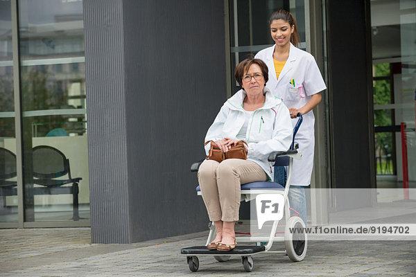 Ärztin schiebt eine Patientin  die auf einem Stuhl sitzt.