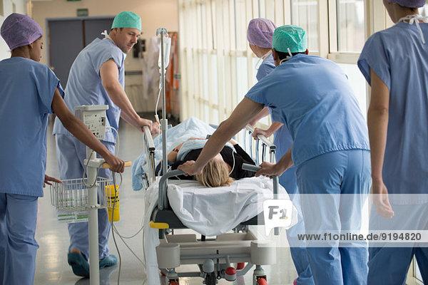 Medizinisches Fachpersonal schiebt den Patienten auf die Trage in einem Krankenhaus