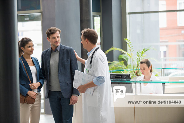 Male doctor discussing with couple at hospital reception desk