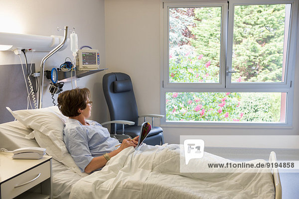 Woman looking through a window on hospital bed