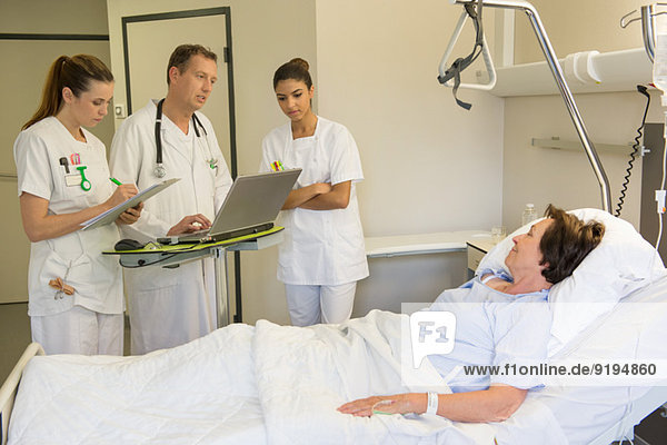 Medical team attending female patient on hospital bed