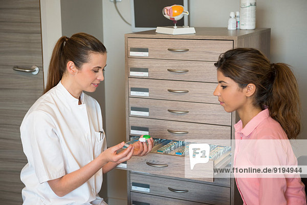Female optician showing contact lens to woman