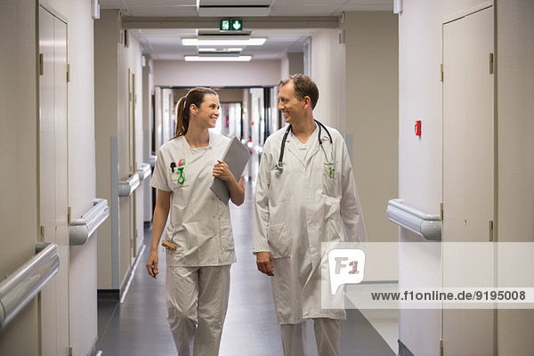 Doctor and female nurse walking in the corridor of a hospital