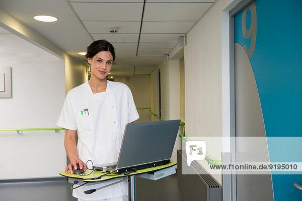 Krankenschwester mit Laptop im Flur des Krankenhauses