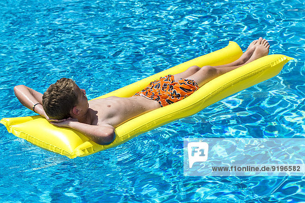 Boy  12 years  lying on a lilo in a swimming pool