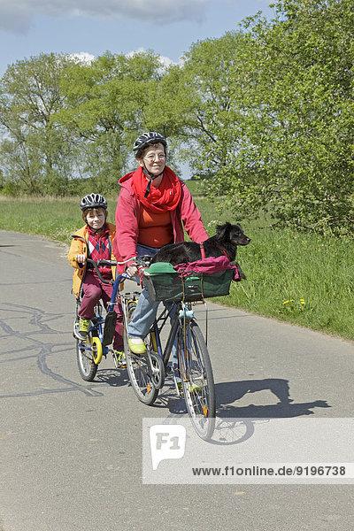 Mutter und Sohn mit Hund auf Radtour
