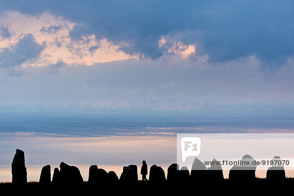 Visitors at the Ale's Stones largest preserved stone ship in Scandinavia  sunset  Kåseberga  Scania  Sweden