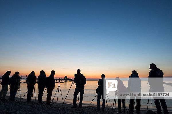 Menschen beim Fotografieren am Strand bei der Seebrücke  Sonnenuntergang  Ostsee  Zingst  Fischland-Darß-Zingst  Mecklenburg-Vorpommern  Deutschland