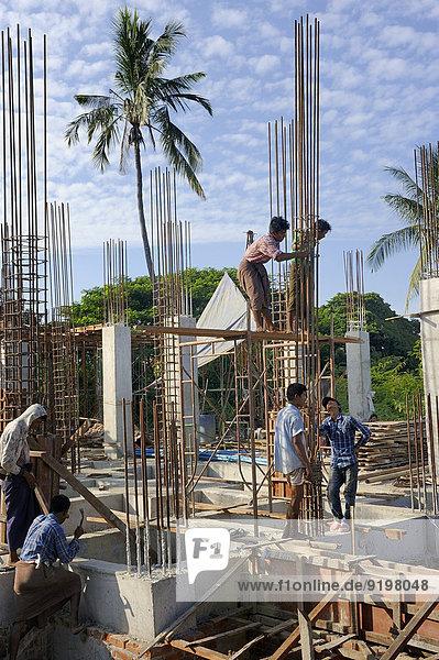 Bauarbeiter auf einer Hochhausbaustelle verdrahten Bewehrungsstahl,  Mandalay,  Myanmar