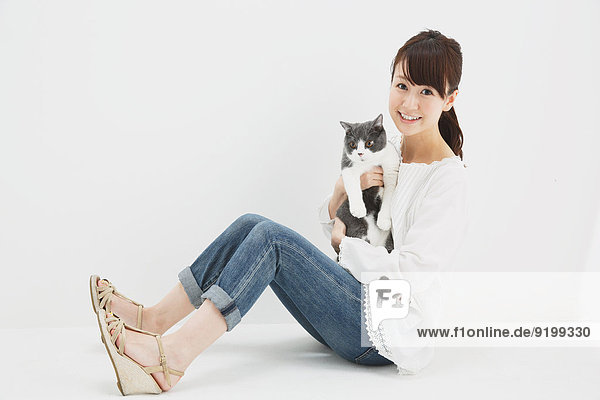 Japanese young woman in jeans and white shirt with cat