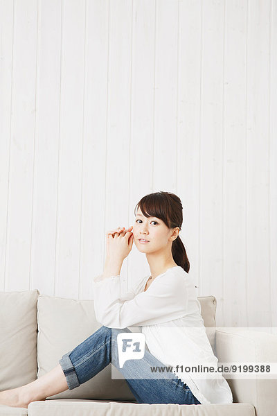 Japanese young woman in jeans and white shirt on the sofa
