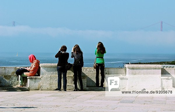 A woman sits reading by the river Tejo while 3 tourists take photos of the April 25th bridge in the mist  Lisbon  Portugal  western Europe.