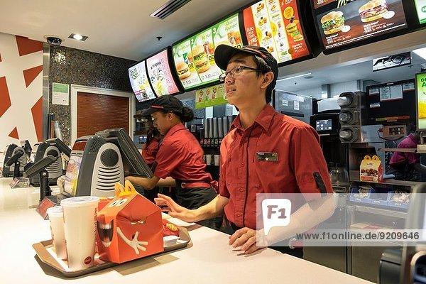 Fast Food takeaway junk Frau Mann Angestellter geben Beruf Restaurant schwarz bestellen Tablett Kollege Hamburger Australien Circular Quay Tresen New South Wales Ordnung Sydney