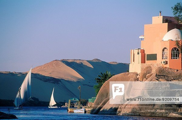 EGYPT.NUBIA.ASWAN.TWO FELUCCAS ON THE NILE. ON RIGHT HOUSE BUILT ON THE ROCKS.