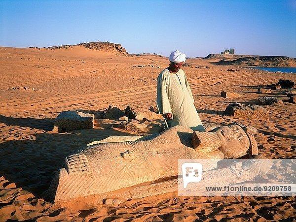 EGYPT.NUBIA.ON LAKE NASIR SHORELINE THE TEMPLE OF WADI EL-SEBUA AT SUNRISE.A TEMPLE WARDEN ADMIRING A FALLEN STATUE OF PHARAOH RAMASSES II.