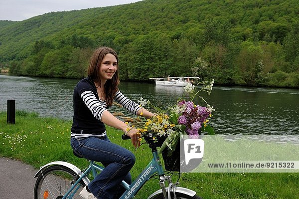 young woman cycling on cycle lane along the Meuse River at Haybes  Ardennes department  Champagne-Ardenne region of northeasthern France  Europe.